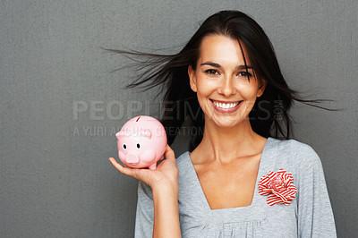 Buy stock photo Smiling woman holding piggy bank in one hand