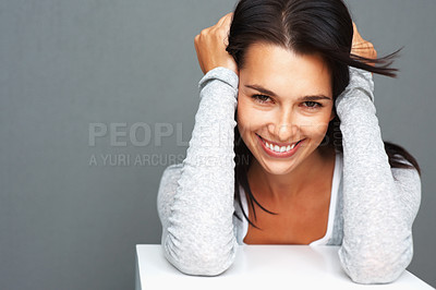 Buy stock photo Pretty woman smiling while leaning on shelf with hands on her head
