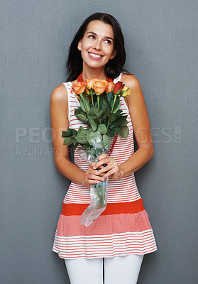 Buy stock photo Woman holding bouquet of roses and smiling while looking in distance