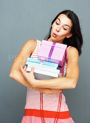 Buy stock photo Pretty woman with surprised expression carrying an armful of gifts, against a grey background