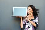Woman presenting laptop while looking surprised