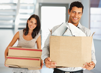 Buy stock photo Happy couple carrying cardboard boxes while shifting their house