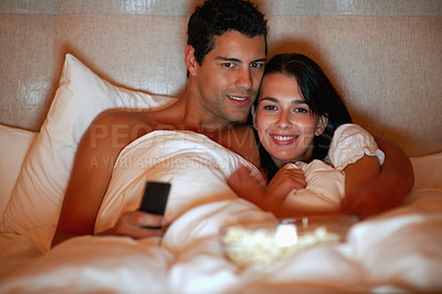 Buy stock photo Portrait of young couple watching television while lying on the bed