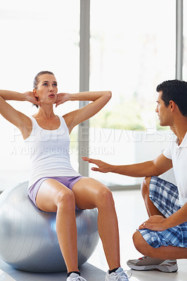 Buy stock photo Male fitness trainer helping woman in doing situps on an exercise ball - copyspace