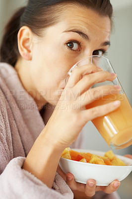 Buy stock photo Closeup portrait of woman drinking juice and holding bowl of cut fruits