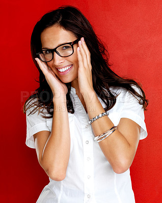Buy stock photo Portrait of an attractive young girl in glasses smiling against red background
