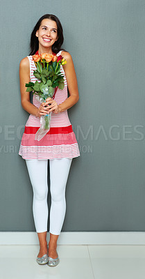 Buy stock photo Full length of pretty young woman holding bunch of flowers and looking away