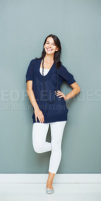 Buy stock photo Full length of smiling young woman posing against the wall