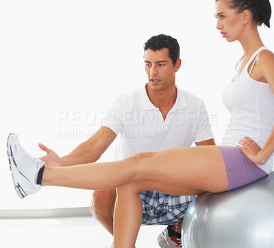 Buy stock photo Happy young woman exercising on fitness ball with personal trainer