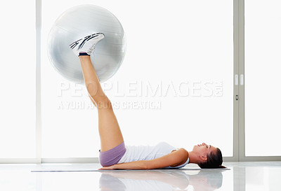 Buy stock photo Side view of active young woman training on fitness ball