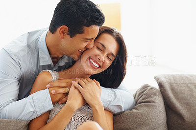 Buy stock photo Portrait of a handsome man hugging his girlfriend from behind