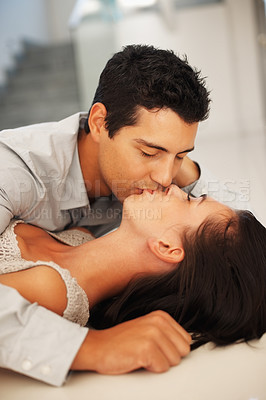Buy stock photo Portrait of young couple kissing indoors