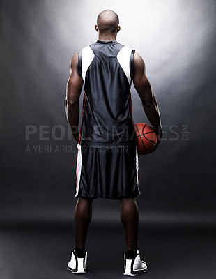 Buy stock photo Rear-view of a young man holding a basketball against a grunge background