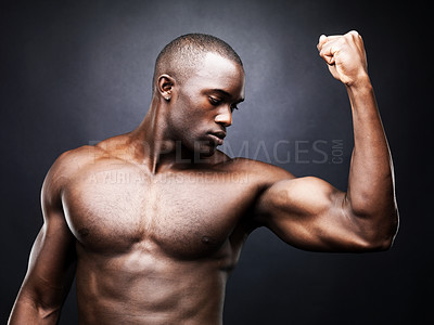 Buy stock photo Portrait of a sexy young African-American man showing his strong biceps against a dark background