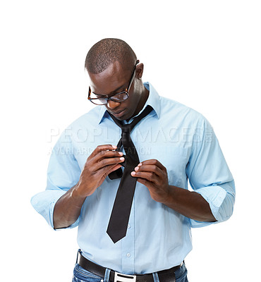 Buy stock photo Portrait of a young African American man putting on a tie against a white background