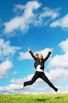 Buy stock photo Cheerful business woman jumping on meadow against blue sky