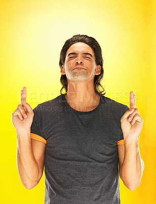 Buy stock photo Handsome man crossing his fingers against yellow background