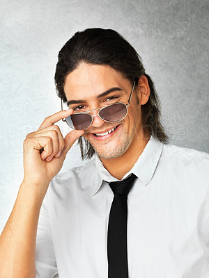 Buy stock photo Close up of man holding sunglasses while smiling against gray background