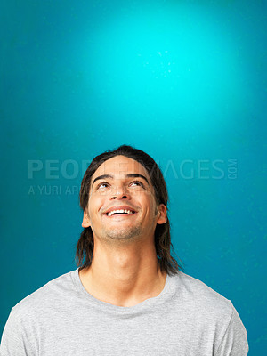 Buy stock photo Attractive man looking up and smiling against blue background