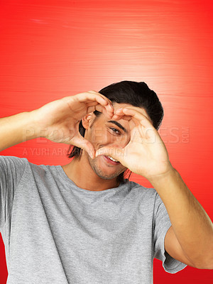 Buy stock photo Portrait of smart man looking through heart sign