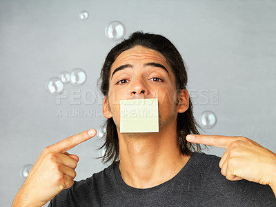 Buy stock photo Portrait of young man pointing fingers towards his mouth with adhesive tape