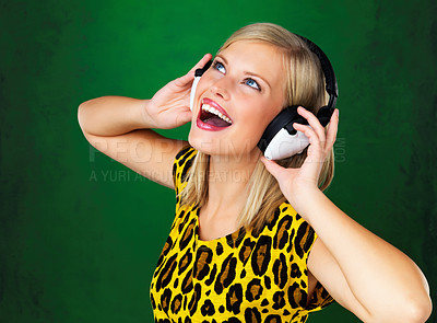 Buy stock photo Pretty woman looking up with headphones on green background