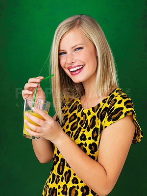 Buy stock photo Attractive woman sipping orange juice against green background