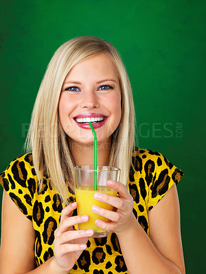 Buy stock photo Closeup of a smiling woman in an animal print t-shirt sipping orange juice, isolated on a jungle green background