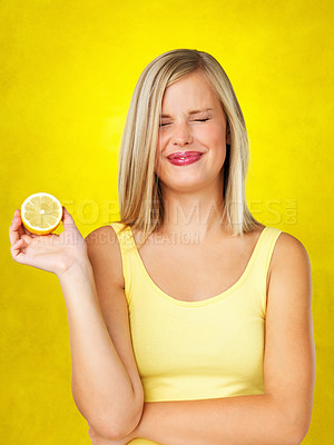 Buy stock photo Woman holding lemon while making a face