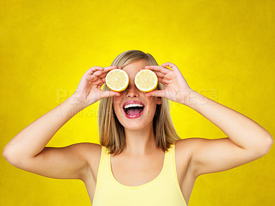Buy stock photo Woman holding lemons up to eyes and smiling