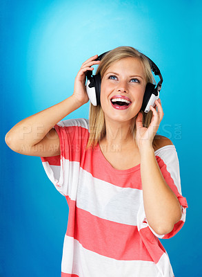 Buy stock photo Pretty blonde woman in a striped red-and-white shirt dancing with headphones on against a blue background