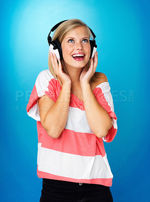 Buy stock photo Pretty woman looking up while wearing headphones