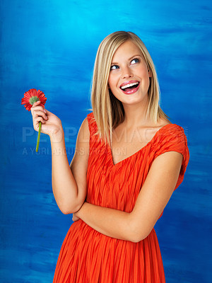Buy stock photo Colourful portrait of a pretty woman holding a flower and looking up smiling excitedly