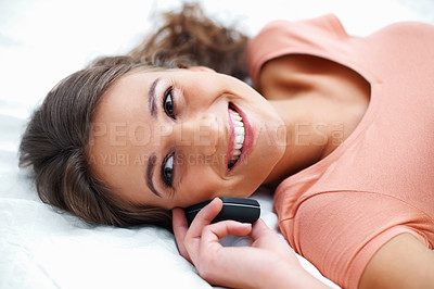Buy stock photo Happy girl with phone looking up while lying on bed