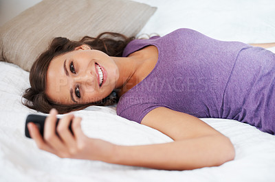Buy stock photo Happy girl reading a text while lying on bed