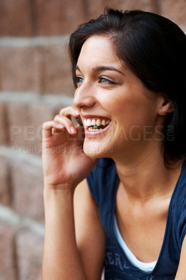 Buy stock photo Portrait of a beautiful young female talking on mobile phone against the wall