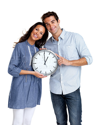 Buy stock photo Portrait of a happy young couple holding a clock in hand against white background