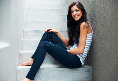 Buy stock photo Portrait of a beautiful young female sitting relaxed on a staircase