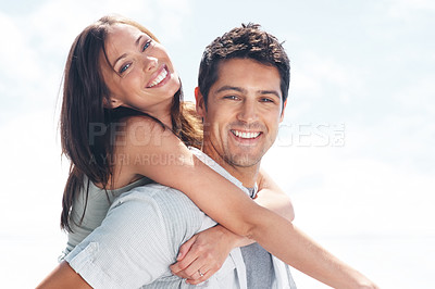 Buy stock photo Portrait of a happy young man piggybacking his cute girlfriend against bright background
