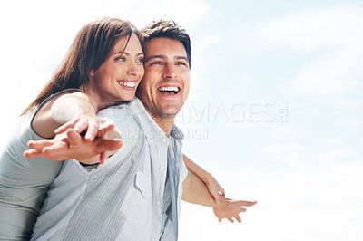 Buy stock photo Smiling young man carrying his beautiful girlfriend on his back with their hands outstretched