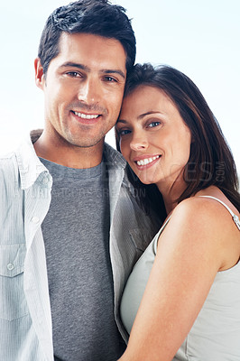 Buy stock photo Portrait of a beautiful young couple standing together against bright background