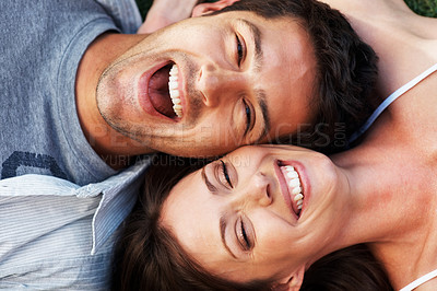 Buy stock photo Topview closeup portrait of a joyful young couple laughing together lying head to head