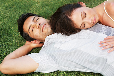 Buy stock photo Portrait of a sweet young couple sleeping together on grass - Outdoor