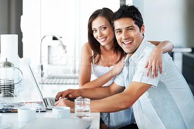 Buy stock photo Portrait of a happy young man working on laptop with his wife in the kitchen at home - Indoor