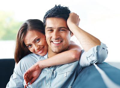 Buy stock photo Portrait of a beautiful young couple smiling together while relaxing on sofa - Indoor