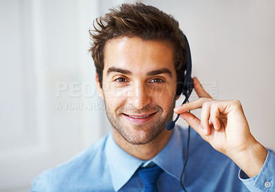 Buy stock photo Closeup portrait of young call center assistant speaking holding his headset and smiling at the camera