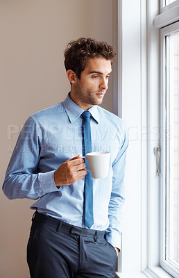 Buy stock photo An executive deep in thought next to a window with his cup of coffee