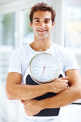 Buy stock photo Portrait of fit young man holding a weight scale and smiling