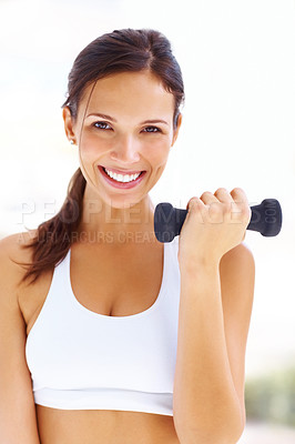 Buy stock photo Portrait of pretty young woman lifting dumbbells and smiling at you - copyspace