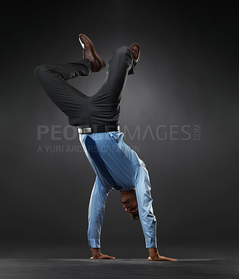 Buy stock photo Full length of business man doing handstand on black background